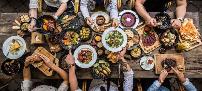 Ljudi-jedu-rostilj-za-stolom